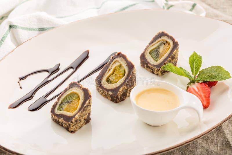 Sobremesa Maki Sushi Chocolate Roll com vários fruto e queijo creme e molho na placa branca imagens de stock