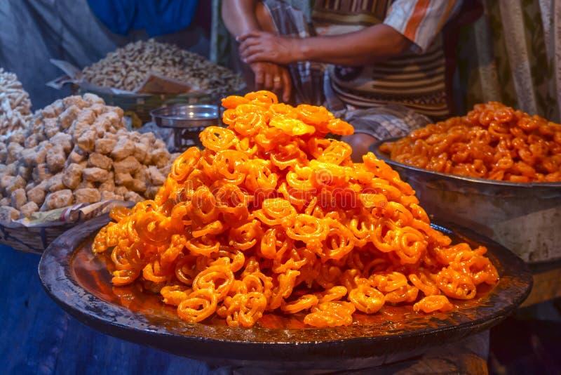 A sobremesa ou os doces indianos tradicionais recentemente cozinhados Jalebi estão vendendo no mercado local imagens de stock