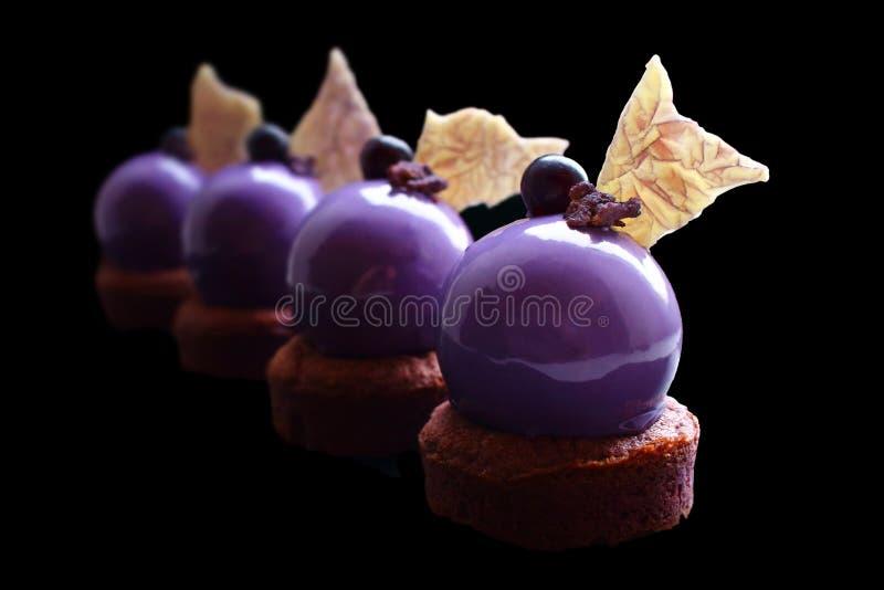 Sobremesa roxa da uva com as decorações brilhantes do esmalte e do chocolate do espelho foto de stock