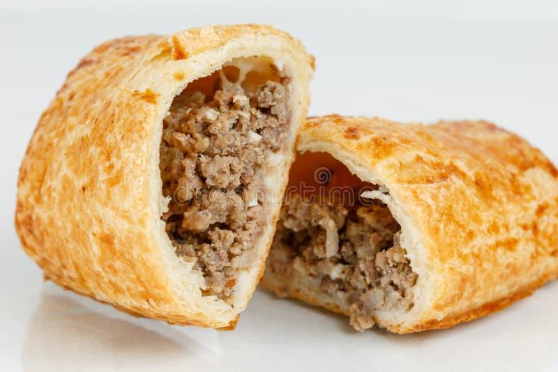 Sobremesa saboroso da massa folhada cortada ao meio Pastelarias deliciosas com carne triturada no fundo claro fotografia de stock
