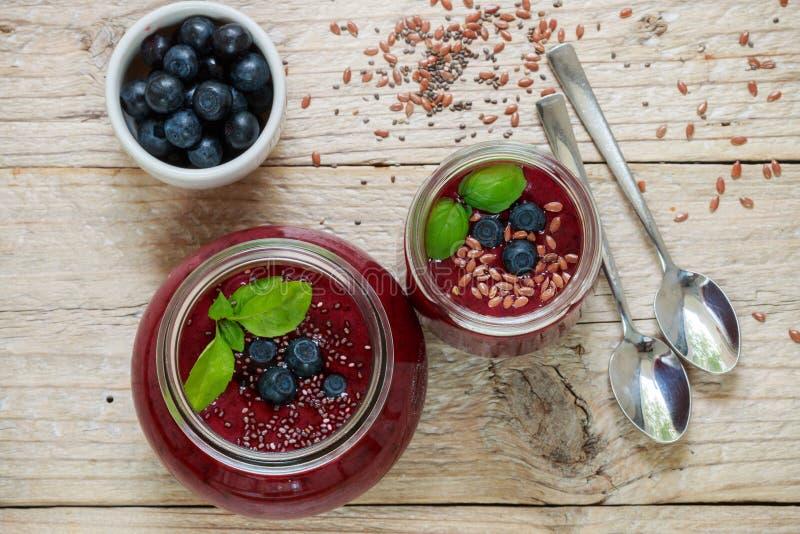 Sobremesa saudável do verão do café da manhã Batidos dos mirtilos com sementes de Chia e semente de linho e bagas suculentas fres imagem de stock royalty free