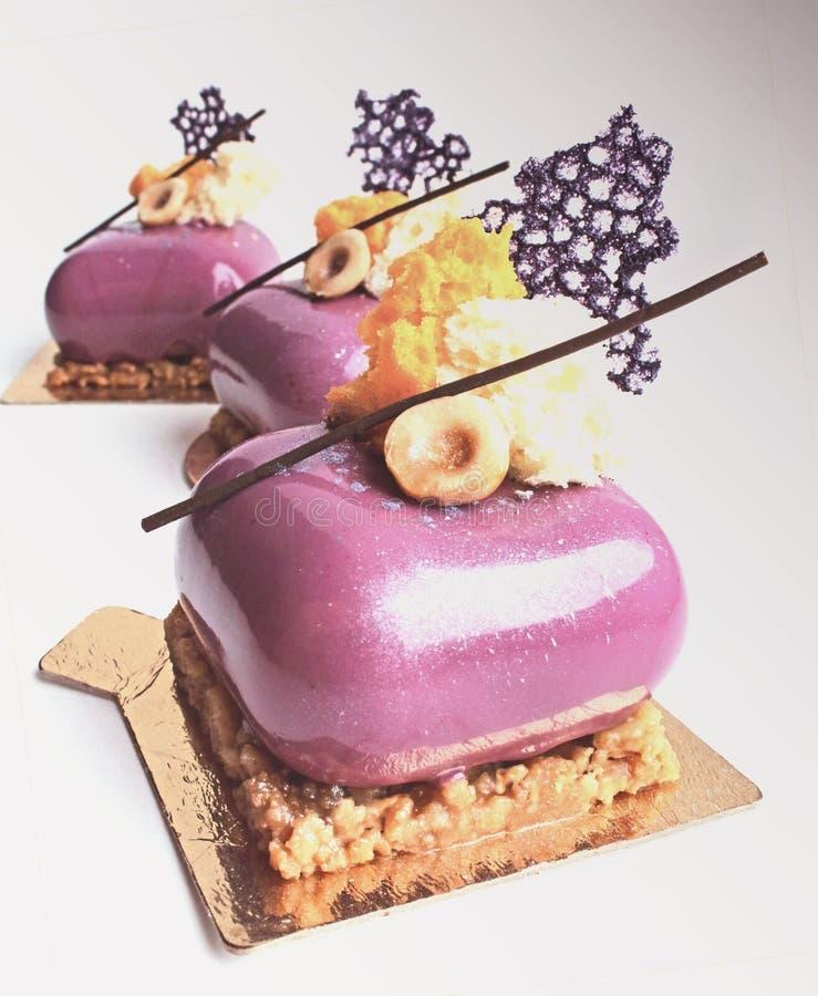Sobremesa vitrificada brilhante com avelã, esponja da micro-ondas e a decoração coral do crepe do laço imagens de stock royalty free