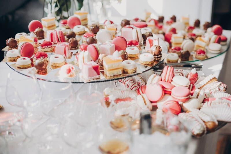 Sobremesas do rosa e as brancas, macarons e queques no suporte, tabela doce moderna no casamento ou festa do bebê Conceito de aba imagens de stock royalty free