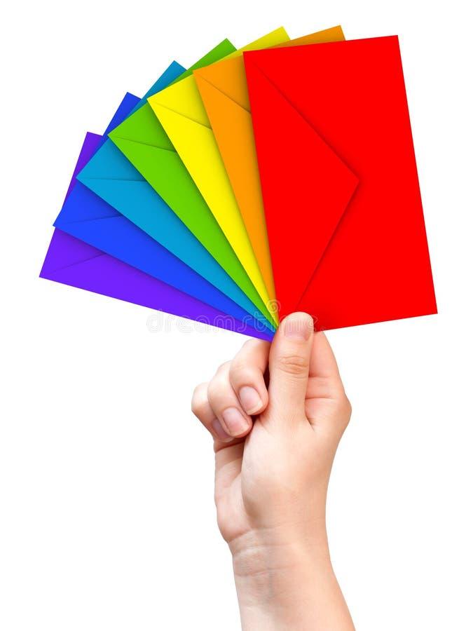 Sobres coloridos en la mano femenina fotos de archivo libres de regalías