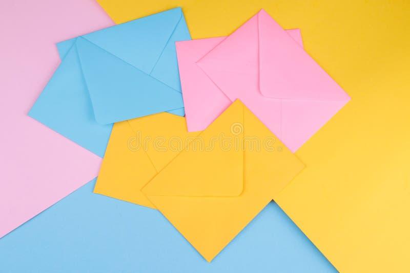 Sobres postales multicolores en un fondo multicolor brillante Visión desde arriba Concepto del correo o de la entrega fotografía de archivo libre de regalías