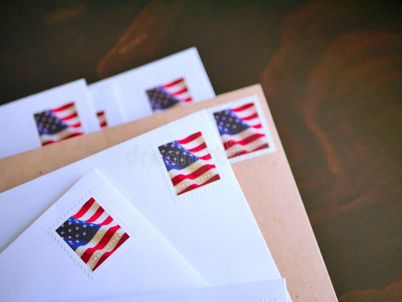 Sobres y efectos de escritorio en blanco con los sellos blancos y azules rojos de la bandera americana fotos de archivo libres de regalías
