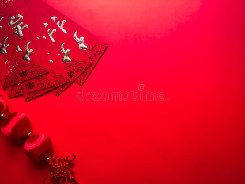 Sobres y nudos chinos rojos del efectivo en fondo rojo foto de archivo