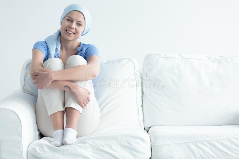 Sobrevivente do câncer que senta-se no sofá fotos de stock