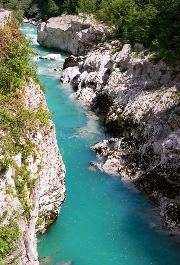 Soca river running between rocks. Emerald Soca river running between rocks near Kobarid royalty free stock image
