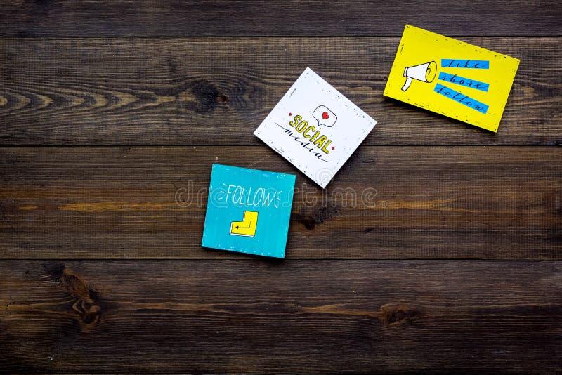 Socail medialne ikony na pracy biurku marketingowy ekspert Cyfrowej promocja towary i usługi Ciemny drewniany tło wierzchołek obraz stock