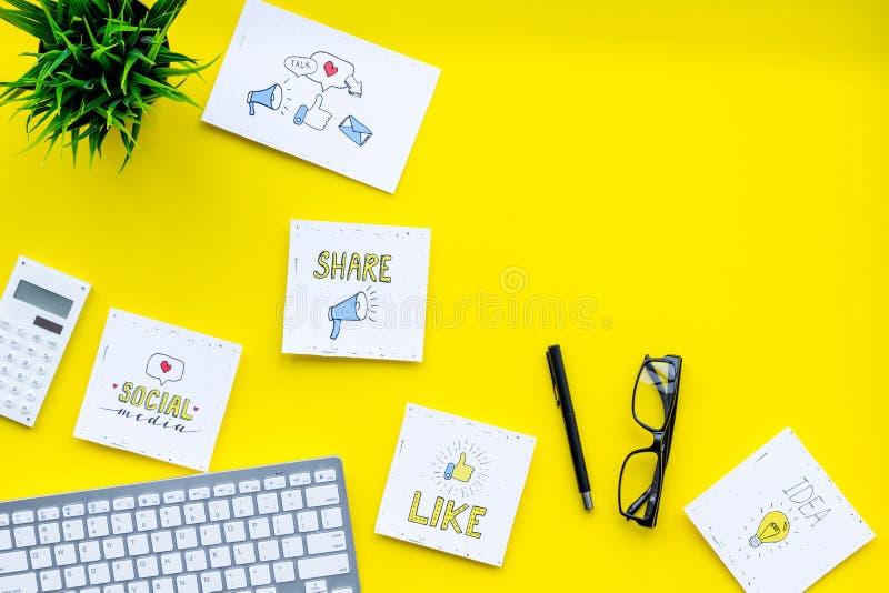 Socailmedia pictogrammen op het werkbureau van deskundige inzake marketing Digitale bevordering van goederen en diensten Gele hoo stock afbeelding
