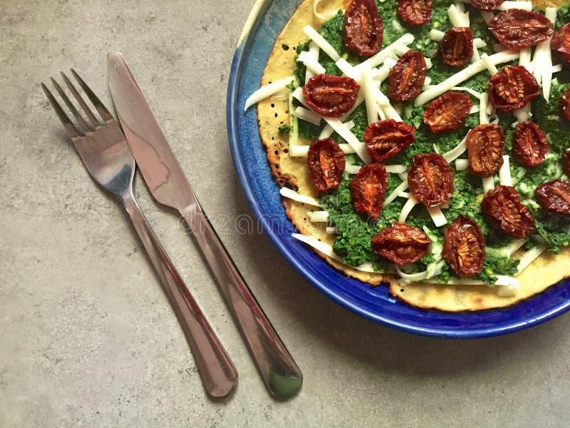 Socca (crêpe de farine de pois chiche) avec le pesto, les tomates et le fromage râpé photo stock
