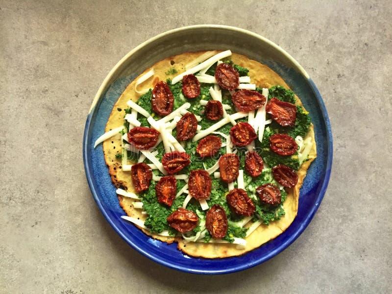 Socca (farinata) med nässla-pistasch pesto, ost och långsam-grillade tomater arkivbilder