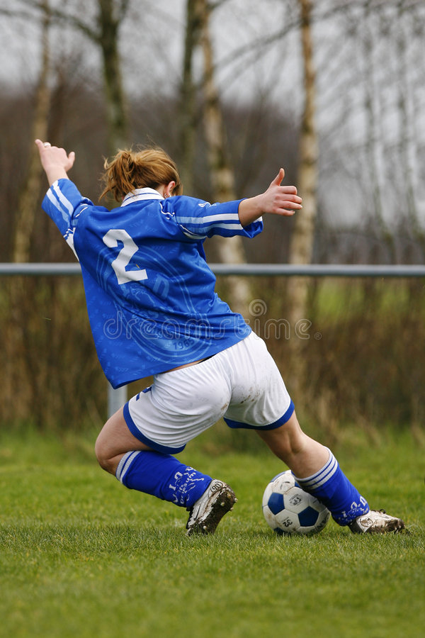 Soccer. Young athletic woman playing soccer and makes an aggressive move to keep the ball in royalty free stock photography
