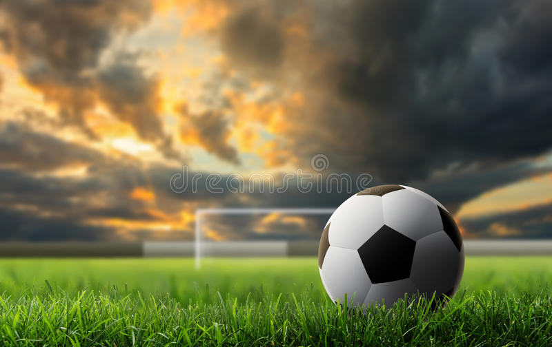 Soccer background. Soccer ball on green grass with sunset background royalty free stock photo