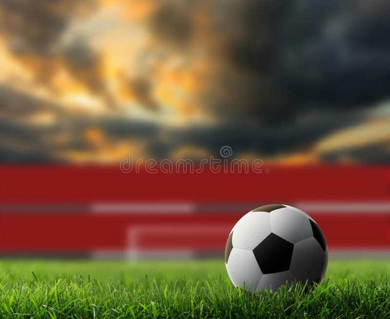 Soccer background. Soccer ball on green grass with sunset background royalty free stock image