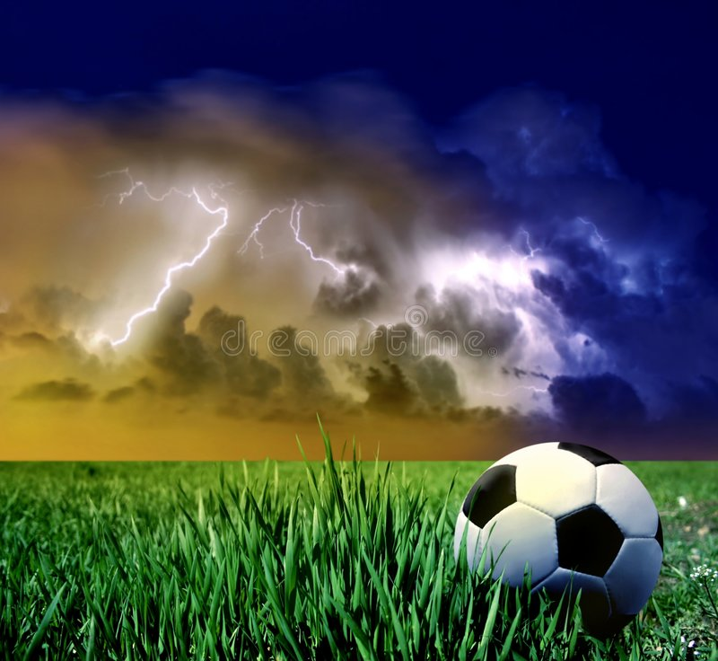 Soccer ball. A soccer ball on the grass field and a storm stock photos