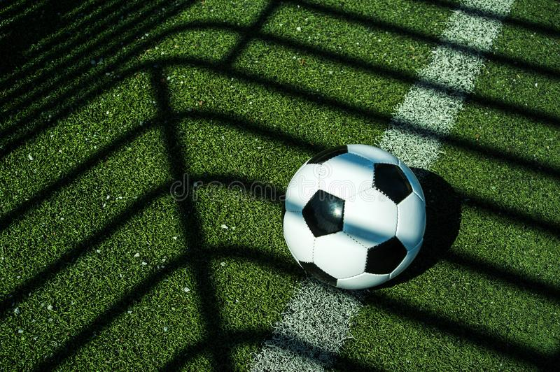 Soccer ball black and white on artificial ground ground with shadows stripes, on the line. For young kids, friends meeting on weekend fun royalty free stock photos