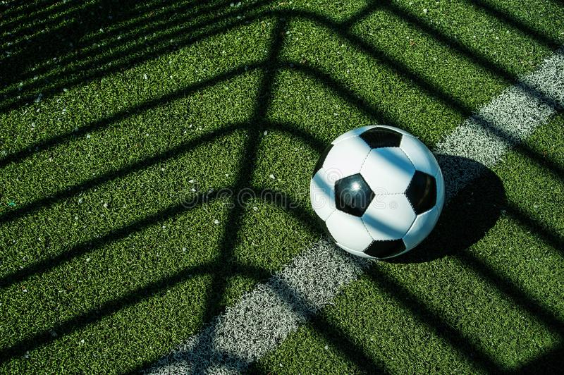 Soccer ball black and white on artificial ground ground with shadows stripes, on the line. For young kids, friends meeting on weekend fun royalty free stock image