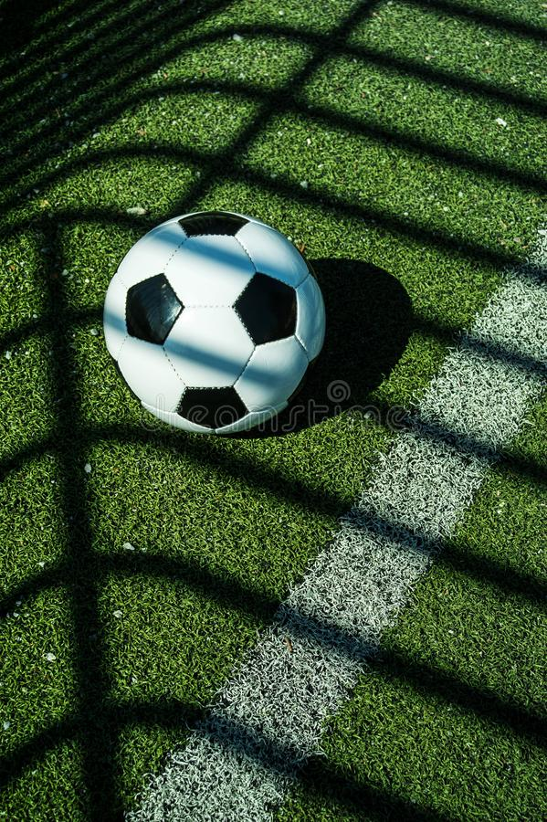 Soccer ball black and white on artificial ground ground with shadows stripes, over the line. For young kids, friends meeting on weekend fun stock image