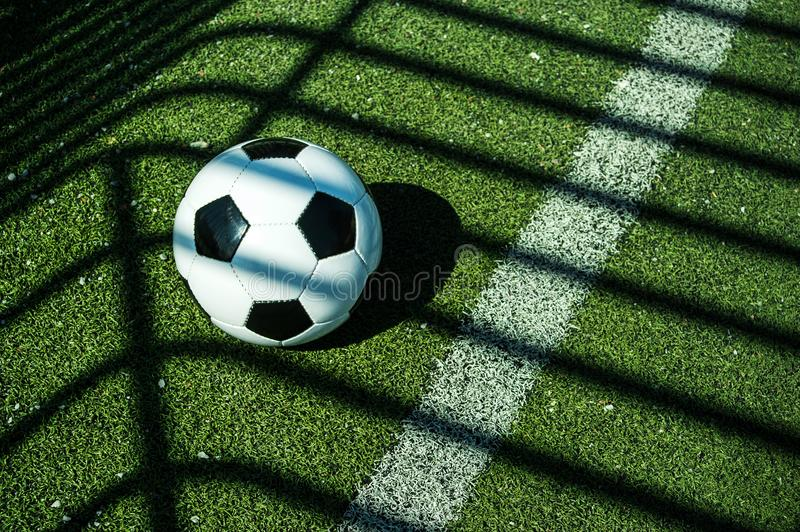 Soccer ball black and white on artificial ground ground with shadows stripes, over the line. For young kids, friends meeting on weekend fun stock photography