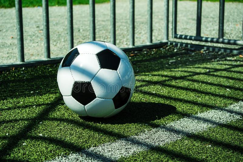 Soccer ball black and white on artificial ground ground with shadows stripes, over the line. For young kids, friends meeting on weekend fun royalty free stock photo