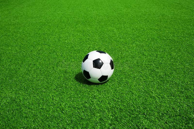 Soccer, football, ball, classic black and white on clean green field, space for text, good for banner. Soccer ball black and white on green artificial turf royalty free stock photography