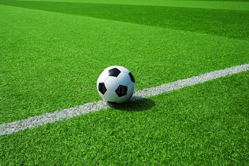 Soccer, football, ball, on white line, mark, classic black and white ball on clean green field, space for text, good for banner. Soccer ball black and white on royalty free stock images