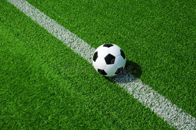 Soccer, football, ball, on line, white mark, classic black and white on clean green field, space for text, good for banner. Soccer ball black and white on green royalty free stock photo