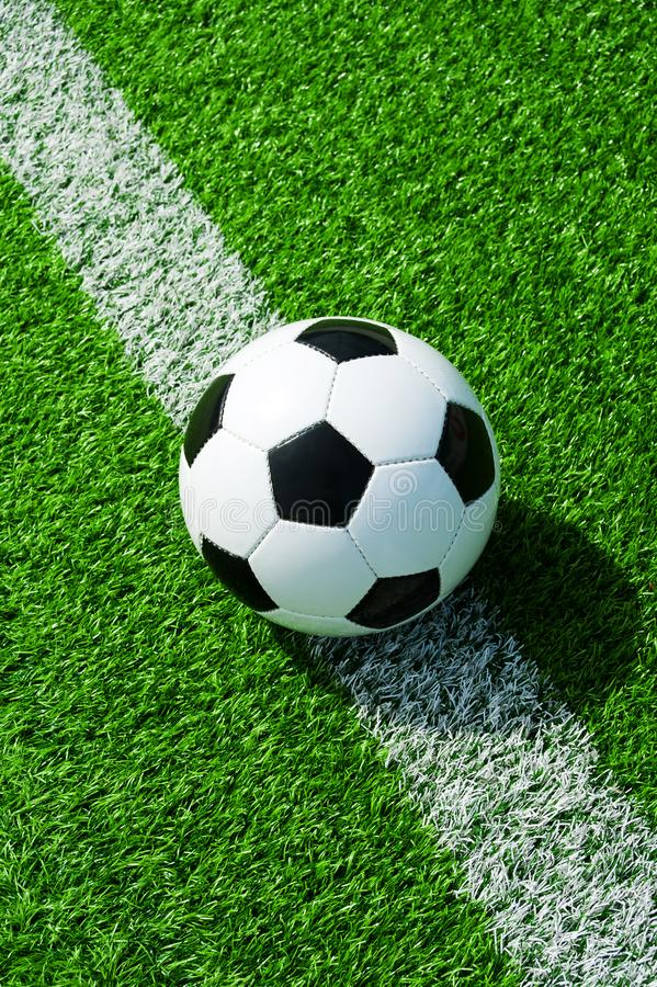 Soccer, football, ball, on line, white mark, classic black and white on clean green field, space for text, good for banner. Soccer ball black and white on green stock images