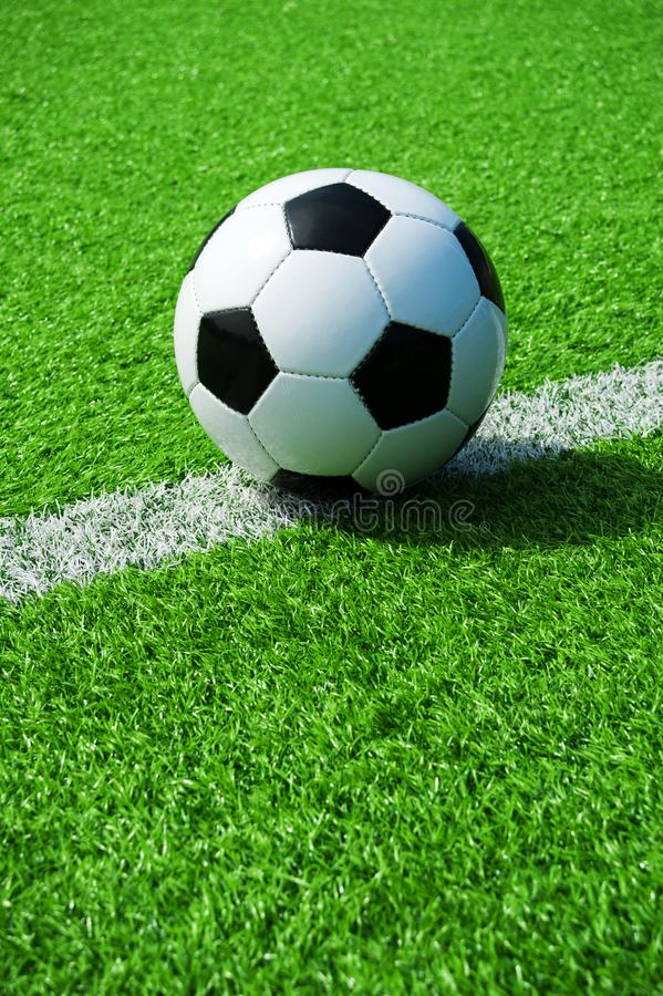 Soccer, football, ball, on white line, mark, classic black and white ball on clean green field, space for text, good for banner. Soccer ball black and white on royalty free stock photography