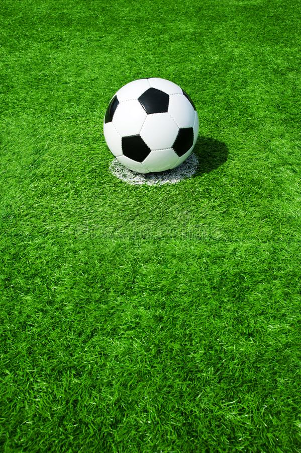 Soccer, football, ball, on penalty spot, classic black and white on clean green field, space for text, good for banner. Soccer ball black and white on green royalty free stock image