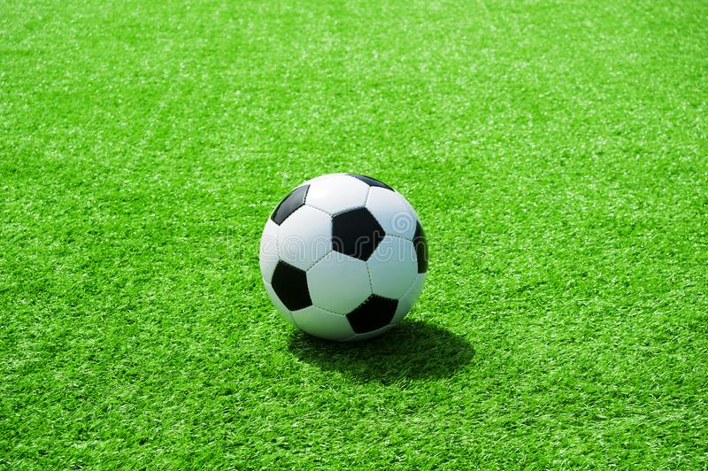 Soccer, football, ball, on penalty spot, classic black and white on clean green field, space for text, good for banner. Soccer ball black and white on green stock images