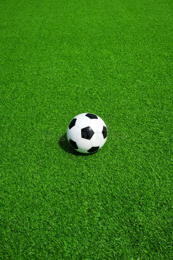 Soccer, football, ball, classic black and white on clean green field with mark, line, space for text, good for banner. Soccer ball black and white on green stock image