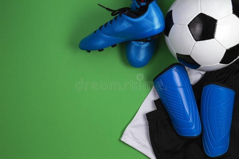 Soccer ball, blue boots, cleats, white t-shirt and black shorts on green background. Flat lay, top view. Soccer ball, boots, cleats, t-shirt and shorts on green stock photography