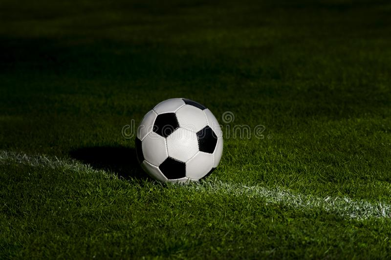 Soccer ball classic in black and white on penalty spot on green artificial turf.  stock photo
