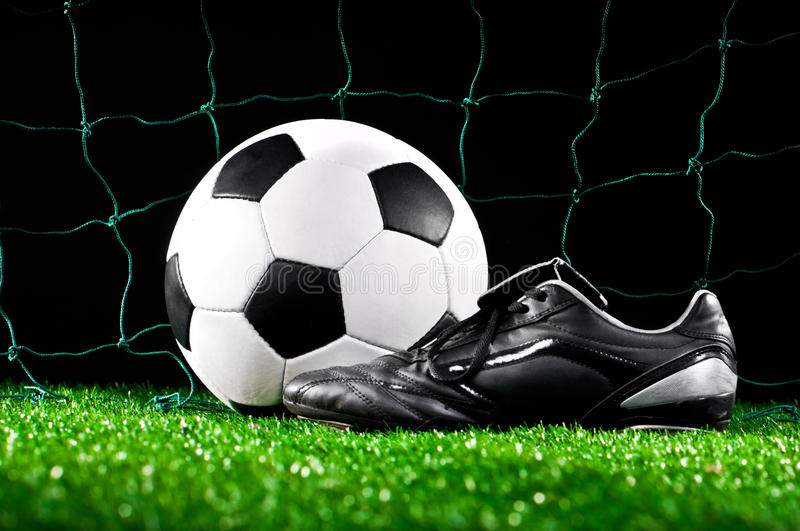 Soccer ball and cleats. On the football field royalty free stock photo