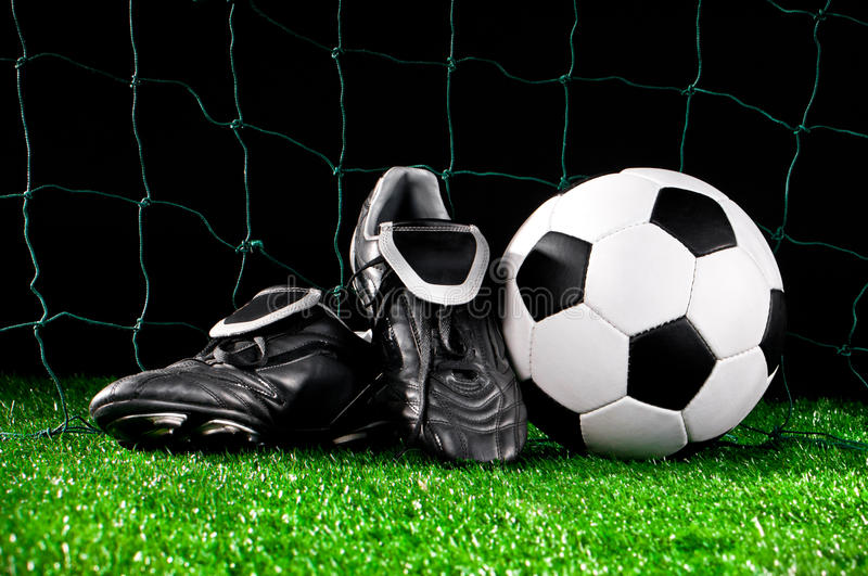Soccer ball and cleats. On the football field stock photography