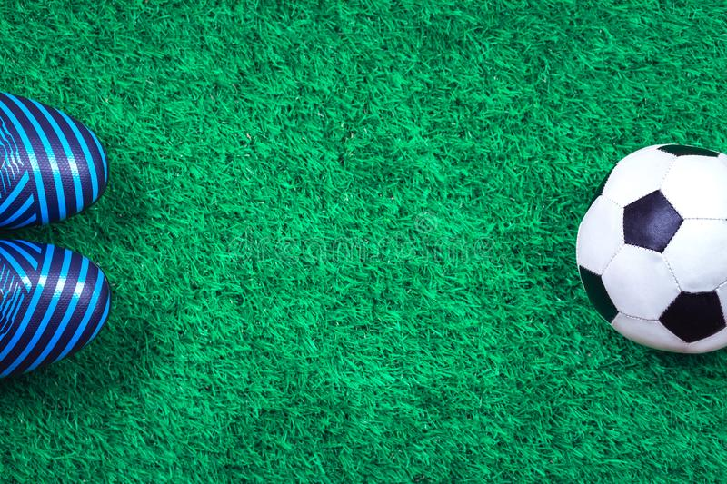 Soccer ball and cleats against green artificial turf. Soccer ball, cleats against green artificial turf, top view with copy space, football concept stock photography