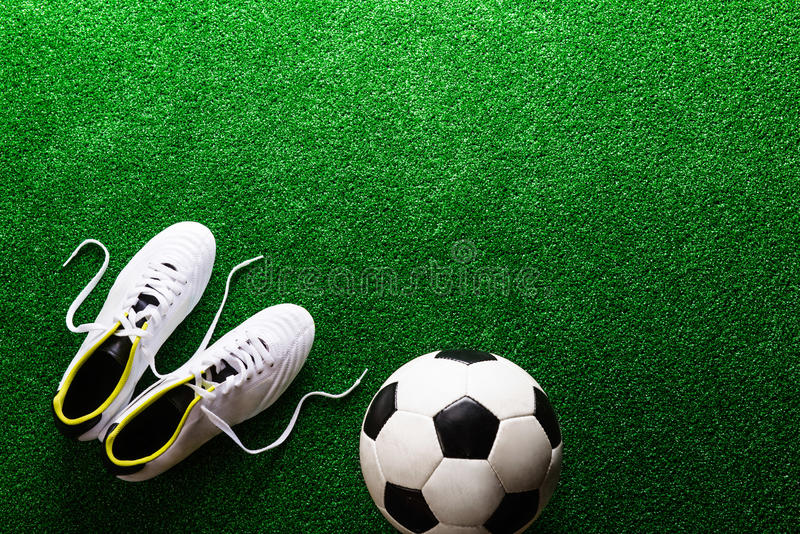 Soccer ball and cleats against green artificial turf, studio sho. Soccer ball and cleats against artificial turf, studio shot on green background. Copy space stock photos