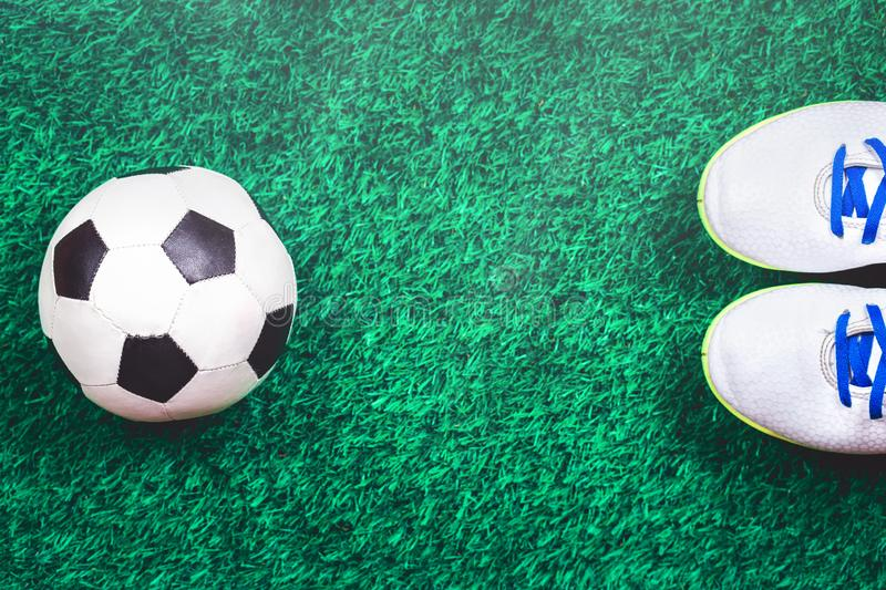 Soccer ball and cleats against green artificial turf. Soccer ball, white cleats against green artificial turf, top view with copy space, football concept stock photography