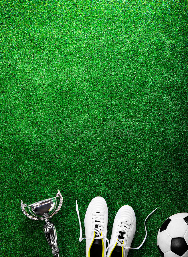 Soccer ball, cleats and trophy against green artificial turf. Soccer ball, cleats and trophy against artificial turf, studio shot on green background. Copy space stock photography
