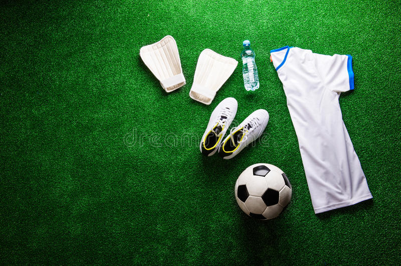 Soccer ball,cleats and various football stuff against artificial. Turf. Studio shot on green background. Copy space stock photos