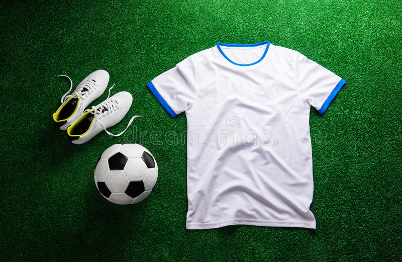 Soccer ball,cleats and white t-shirt against artificial turf. Soccer ball, cleats, white t-shirt against artificial turf. Studio shot on green background. Flat stock images