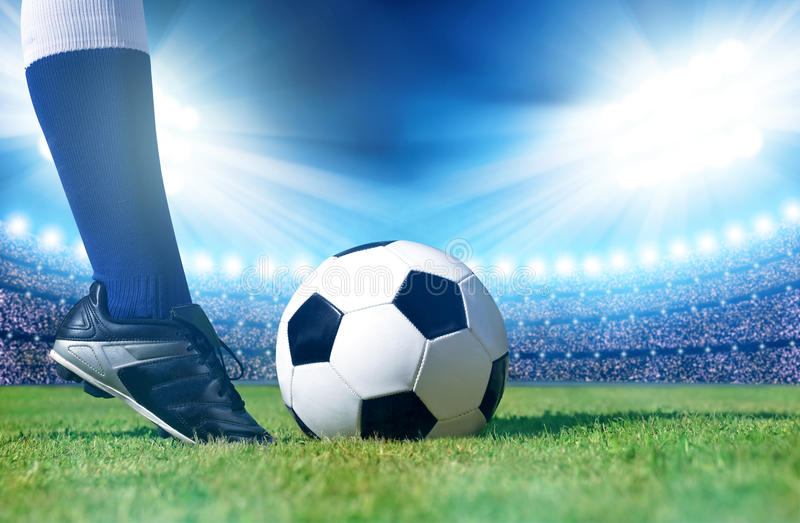 Soccer ball with feet player on the football field. Soccer ball with feet player on the football field in stadium royalty free stock images