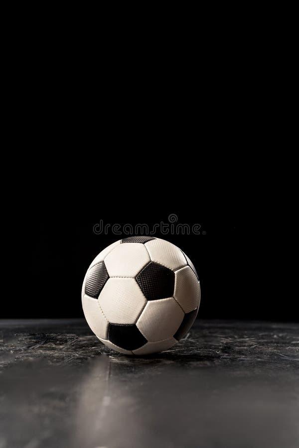 Soccer ball on floor. Single soccer ball on black floor on black background royalty free stock images