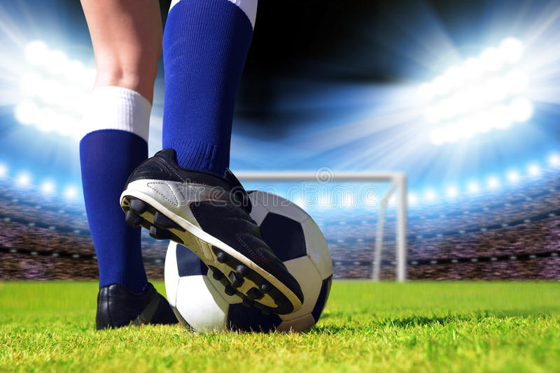 Soccer ball and foot of football player. Soccer ball and football player on the playground royalty free stock images