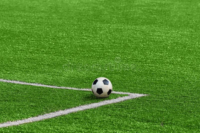 A soccer ball framed by white corner markings on a green football field. royalty free stock photo