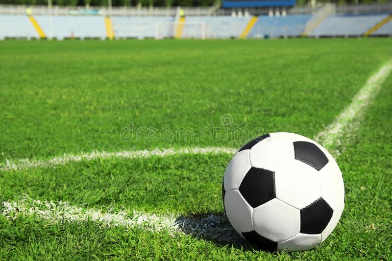Soccer ball on fresh green football field grass. Space for text royalty free stock photo