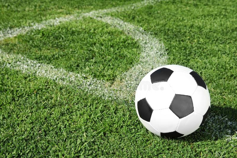 Soccer ball on fresh green football field grass. Space for text royalty free stock photography